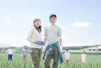 畑に立つ農家の三世代家族