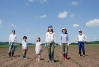 畑に立つ三世代家族