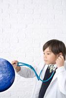 地球に聴診器をあてる白衣の男の子