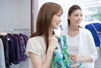 ブティックで洋服を選ぶ20代女性と店員