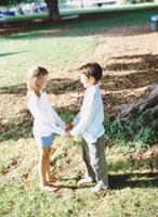手を繋ぎ向き合う外国人の男の子と女の子