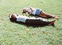 芝生に寝転ぶ外国人の男の子と女の子