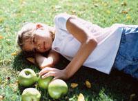 芝生に寝転ぶ外国人の女の子とリンゴ 10161005435| 写真素材・ストックフォト・画像・イラスト素材|アマナイメージズ