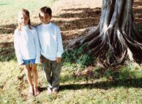 大木のそばに立つ外国人の男の子と女の子