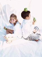 背中合わせで座る外国人の男の子と女の子 10161005443| 写真素材・ストックフォト・画像・イラスト素材|アマナイメージズ
