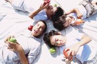 リンゴを持って寝転がる4人の男の子 10161005448| 写真素材・ストックフォト・画像・イラスト素材|アマナイメージズ