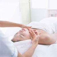 日本人女性の顔をマッサージするエステティシャンの手