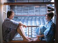 窓辺に座る浴衣姿の日本人カップル