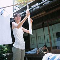 洗濯物を干す女性と縁側で寝転ぶ男性