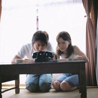 電話を見つめる日本人カップル
