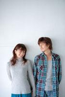 壁にもたれて立っているカップル