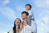 青空の下で笑う親子3人