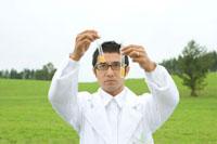 草原で2本の試験管を見る白衣の男性
