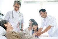 患者を見守る家族と医師