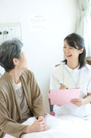 年配患者と話す笑顔の看護師