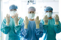 手を上げる手術服の外科医