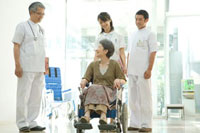 車椅子の年配患者と医師