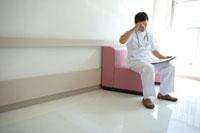 イスに座りカルテを見る医師