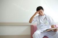 資料を見つめる医師