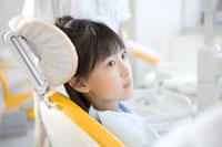歯科の治療用イスに座る少女