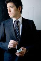 タバコを手にするビジネスマン 10161008640| 写真素材・ストックフォト・画像・イラスト素材|アマナイメージズ