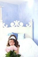 花束を持って座る5歳の女の子