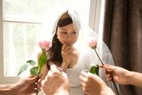 花と指輪を差し出されたウエディングドレス姿の女性