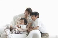 スマートフォンを楽しむ幼い兄弟と母親