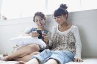 二人でスマートフォンを楽しむ女子大生