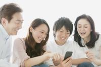 スマートフォンを操作する息子と見つめる家族