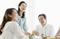食卓を囲み談笑する家族