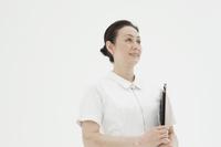 白バックに立つベテラン看護師