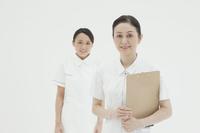 白バックに立つベテラン看護師と新人看護師