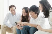 ソファーでスマートフォンを楽しむ家族