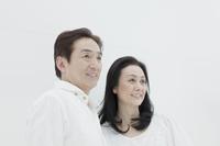白バックで微笑み見つめるシニア夫婦