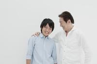 白バックで肩を組む父親と息子