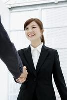 握手するスーツ姿の女性