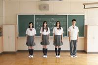 黒板をバックに立つ高校生