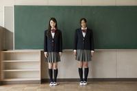 黒板をバックに立つ女子高生