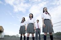 空と雲を背景に立つ高校生