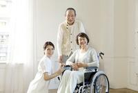 微笑む車椅子のシニア女性夫婦と女性介護士