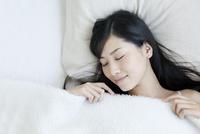 ベッドで睡眠をとる女性