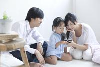 スマートフォンを楽しむ若夫婦と娘