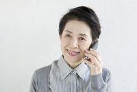 スマートフォンで話している60代女性 10161011708  写真素材・ストックフォト・画像・イラスト素材 アマナイメージズ