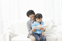 ソファーで本を読む祖母と孫