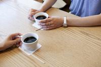 カフェでコーヒーを飲む女性達の手