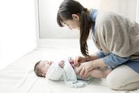 オムツを替える母親と赤ちゃん