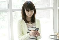 携帯電話を操作する10代女子大生