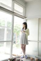 窓際でコーヒーを飲む10代女子大生 10161012233  写真素材・ストックフォト・画像・イラスト素材 アマナイメージズ