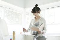 本を見ながら料理する10代女子大生